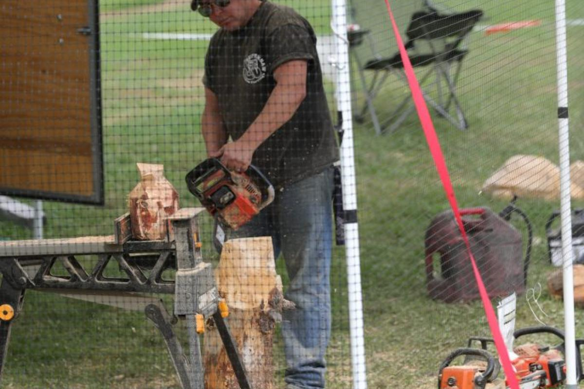 man carving wood with chainsaw